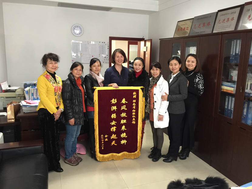 Chen Li (third from left) and her fellow group members hold a silk banner at an office of the Hunan Province Women's Federation in Changsha, Hunan province, Dec. 4, 2016. Yan Jie/Sixth Tone