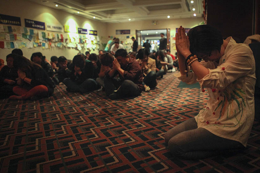 Xu Jinghong prays with other families of MH370 passengers at the Metropark Lido Hotel, where Chinese relatives were put up by Malaysia Airlines following the plane's disappearance, Beijing, April 4, 2014. Quan Yi/Sixth Tone