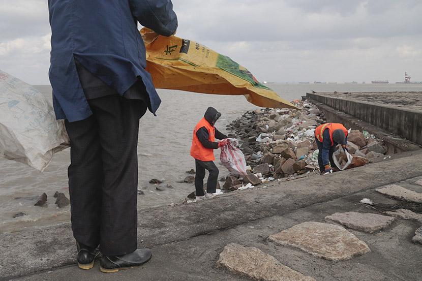 Sanitation workers pick up garbage along the banks of the Yangtze River, Taicang, Jiangsu province, Dec. 27, 2016. Li You/Sixth Tone