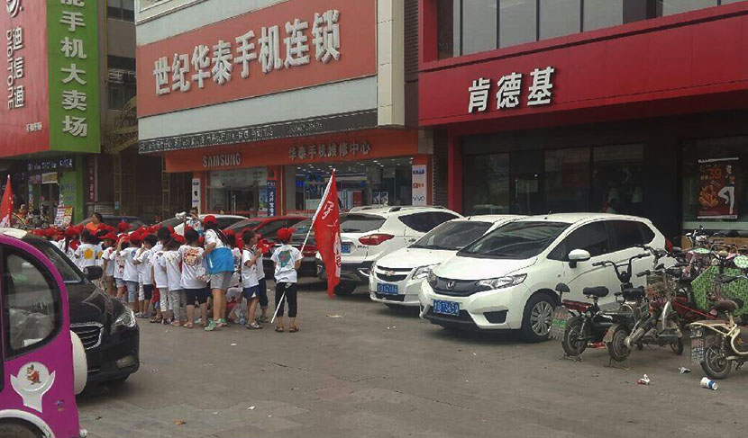 A photo posted on Weibo shows young children in red caps and white shirts standing in front of a KFC restaurant in Tengzhou, Shandong province, July 19, 2016. @Wangshisubao from Weibo
