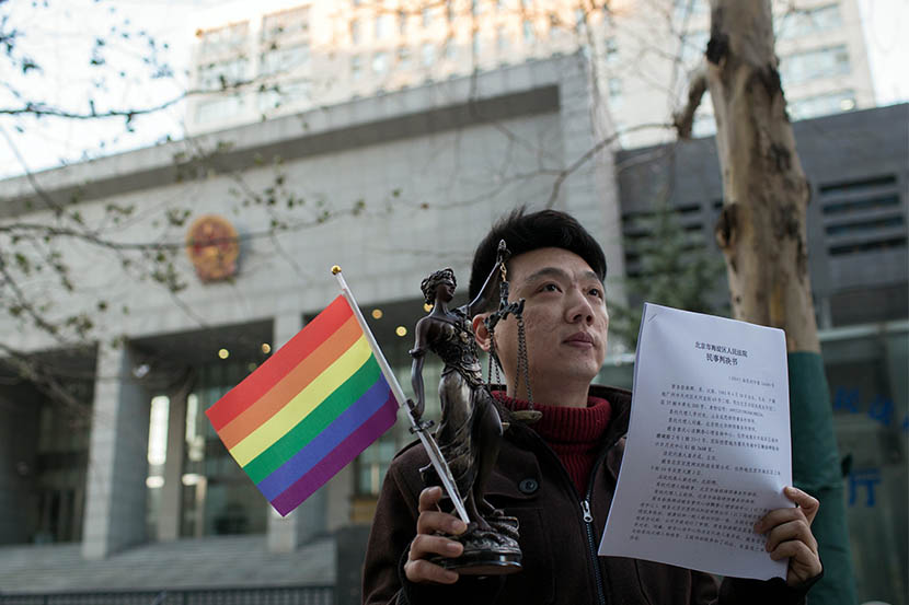 Yang Teng holds a Lady Justice statue and a rainbow flag as he shows the court verdict in front of the Haidian District People's Court, Beijing, Dec. 19, 2014. Yang had successfully sued a clinic that carried out electroshock therapy on him. Xiao Muyi/IC