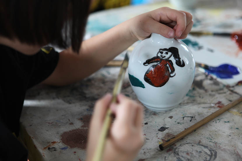 A Jiabeicun student paints a piece of pottery in Jingdezhen, Jiangxi province, July 19, 2016. Andy Boreham/Sixth Tone