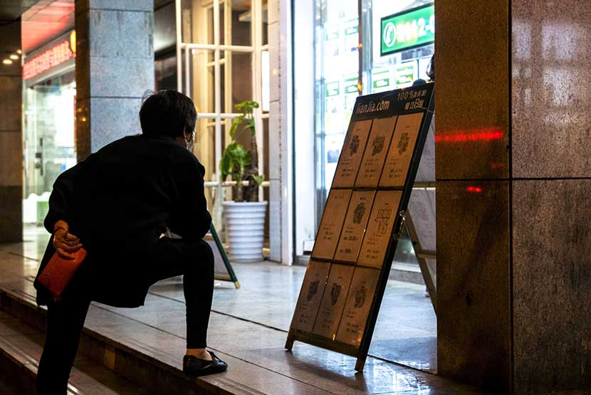 A woman reads an information board with notices of apartments for sale by Lianjia, a large Chinese real estate company, Shanghai, April 18, 2016. In February, home prices in the city jumped 20 percent from the previous year. Zhang Peng/LightRocket via Getty Images/VCG