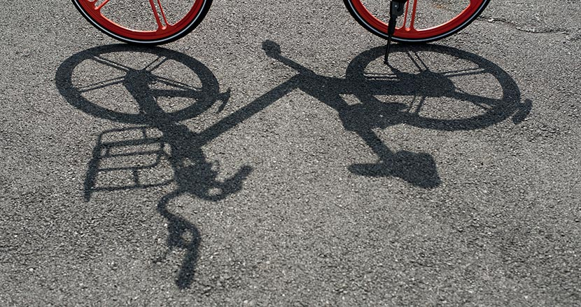 The shadow of a Mobike shared bicycle is seen on the ground, Shanghai, Aug. 13, 2016. Long Liu/VCG