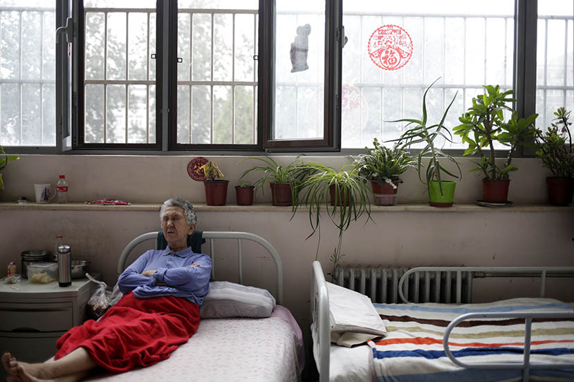 A woman rests in bed at the Songtang Hospice, Beijing, July 19, 2016. The plants by the window were donated by hospice volunteers. Han Meng/Sixth Tone