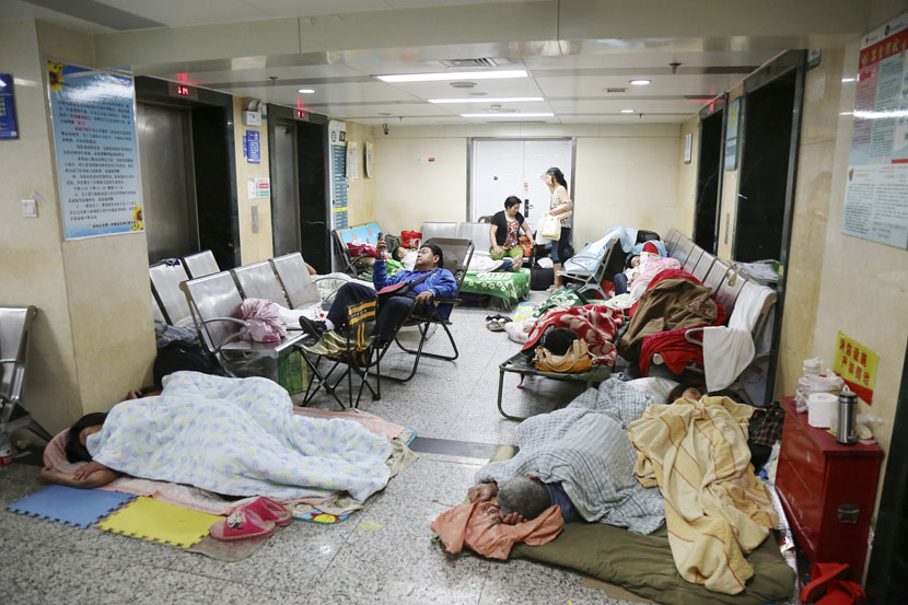 Relatives of patients sleep along the corridor of a 'super hospital,' the First Affiliated Hospital of Zhengzhou University, Henan province, July 3, 2015. Wen Jun/VCG